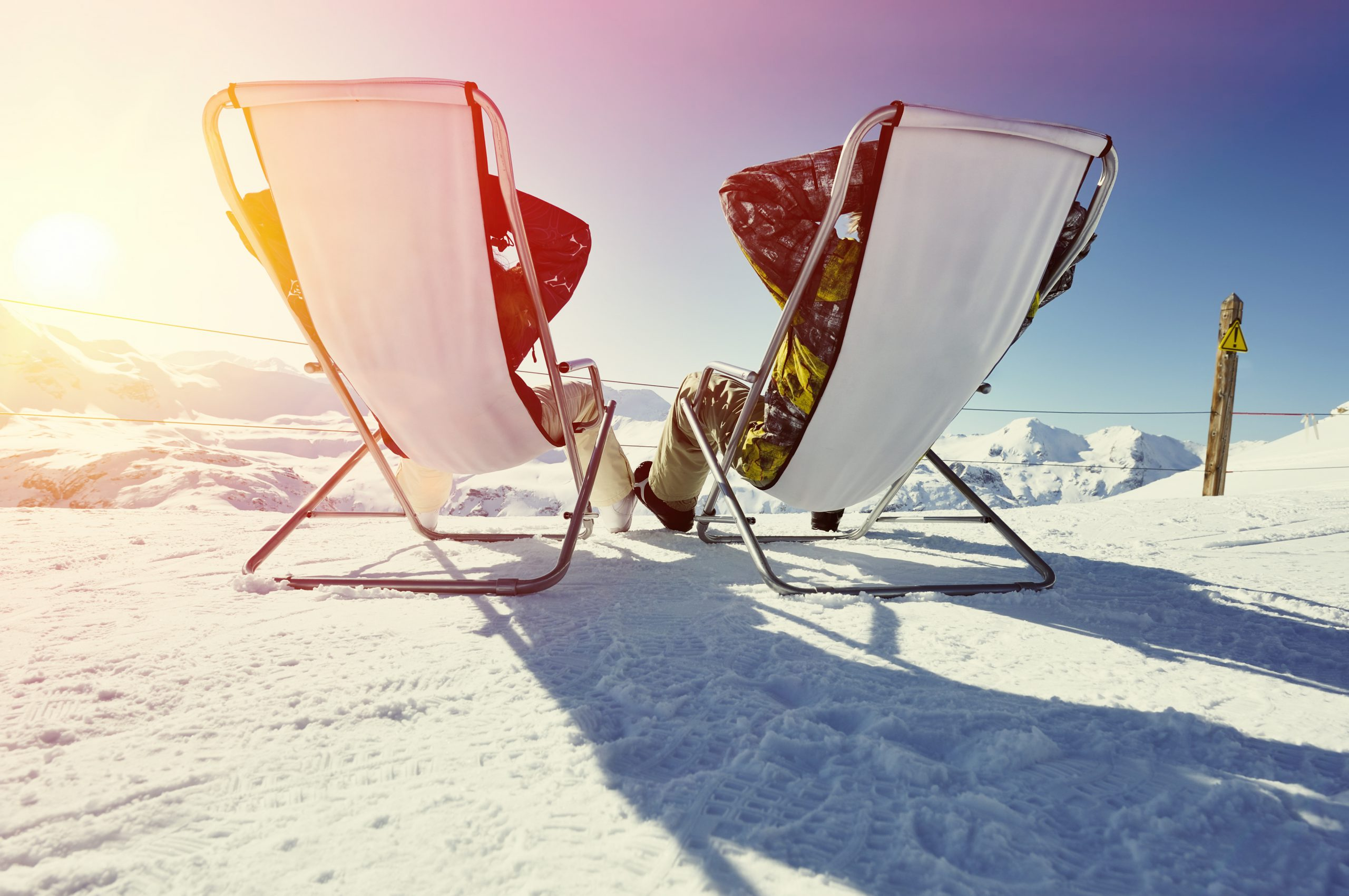 Couple sit in sun loungers looking at mountain in Val d'isere