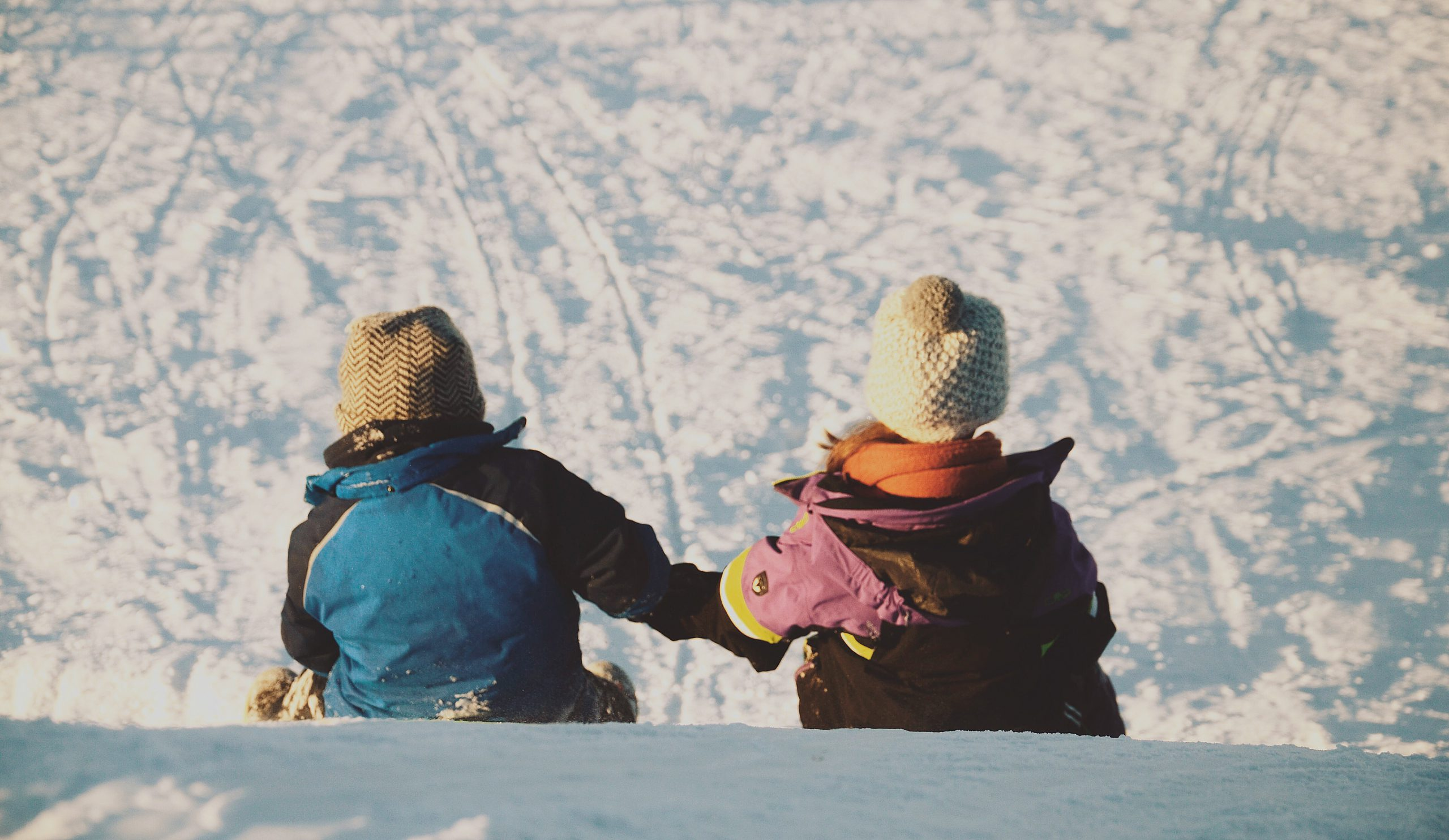 Children in winter ski clothing sitting on snow holding hands