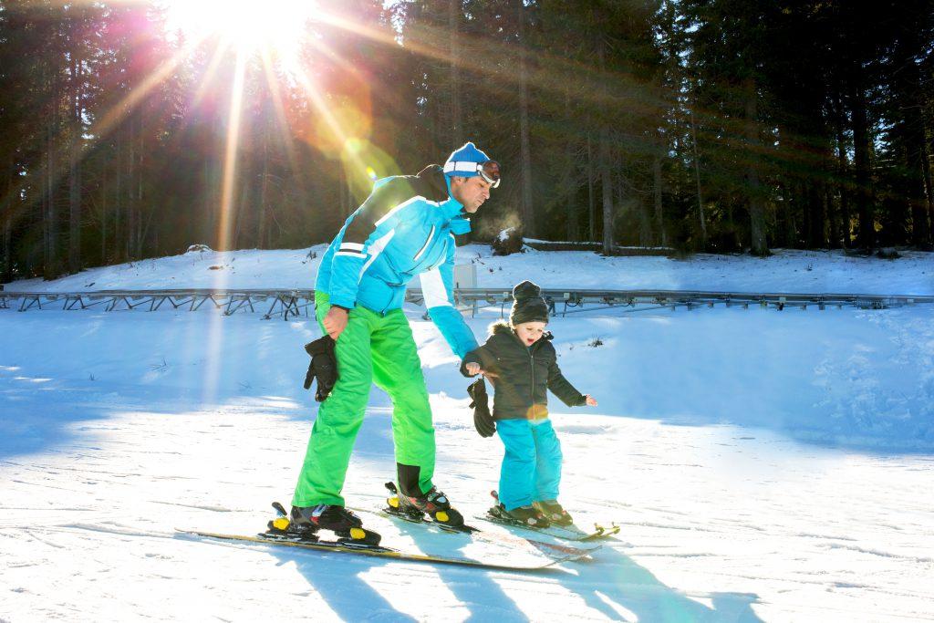 Ski trainer teaching kid to ski while spending day on a mountain.