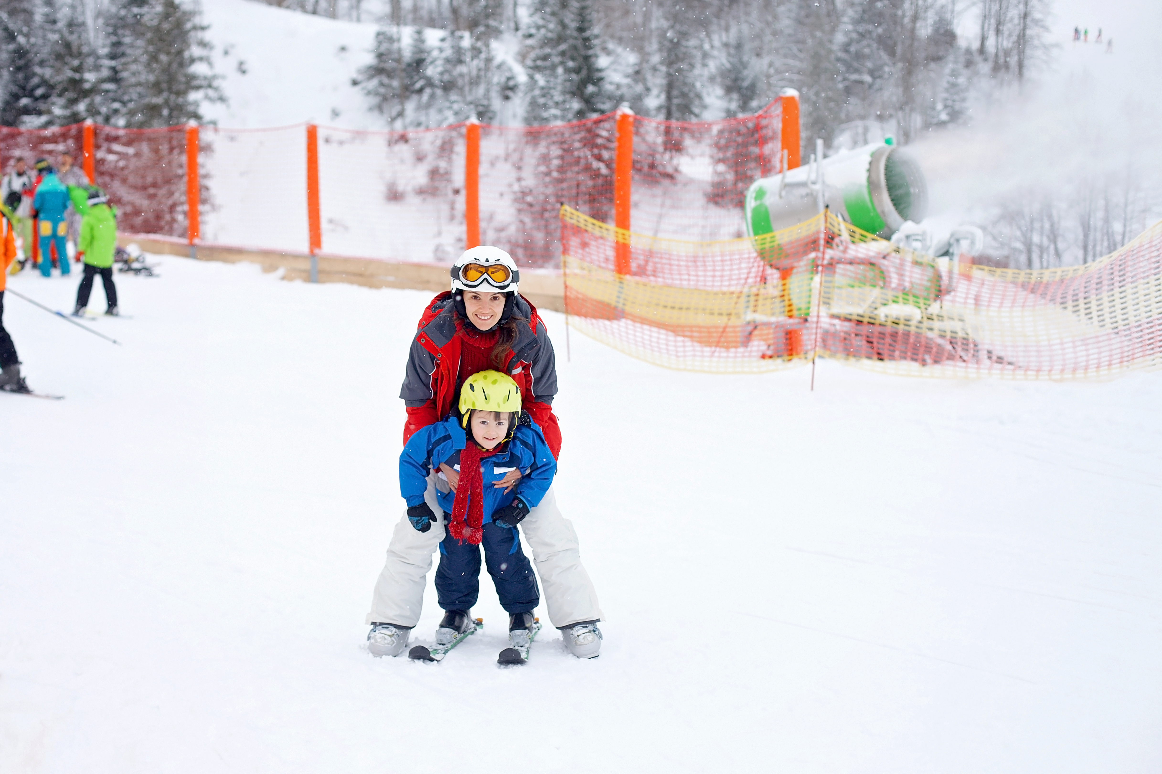 Beautiful young mom and her toddler boy, learning to ski in the mountains, winter time