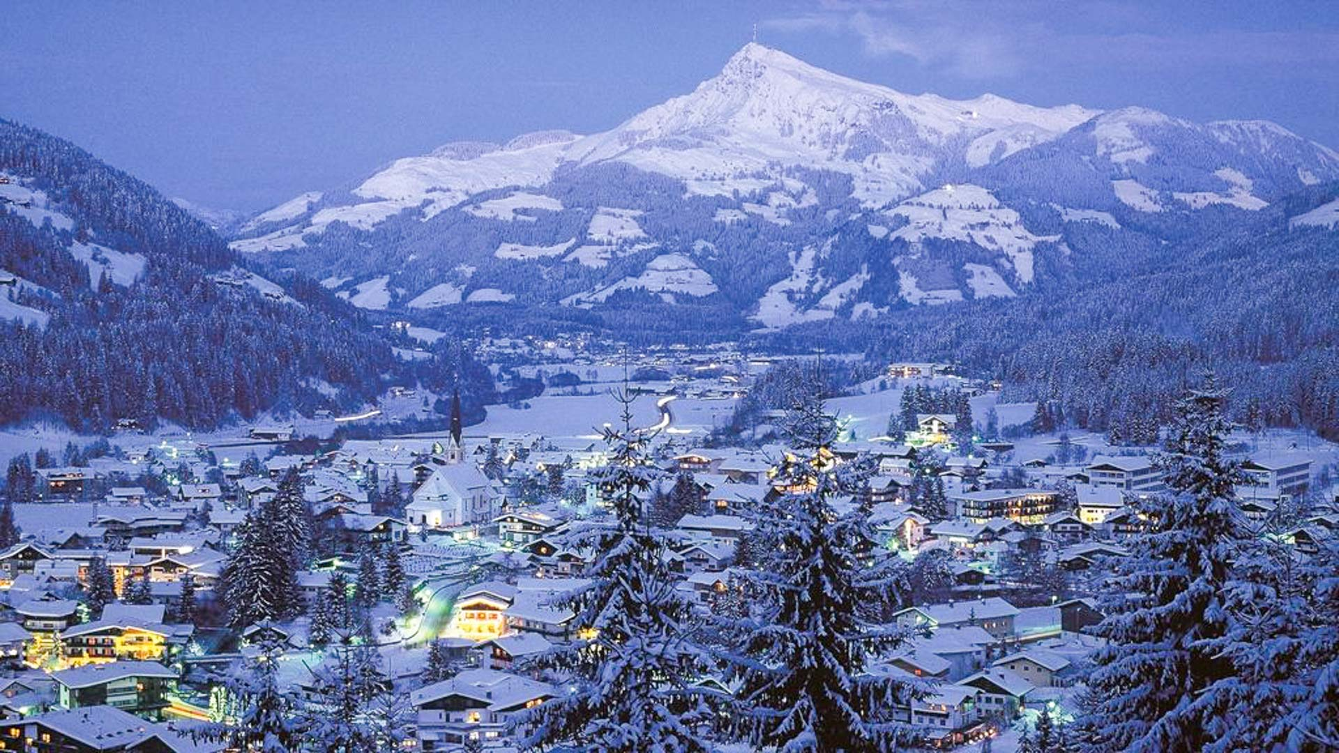 The beautiful Alpine ski village of Kirchberg with glowing lights in the window just after dusk and the ski area visible behind