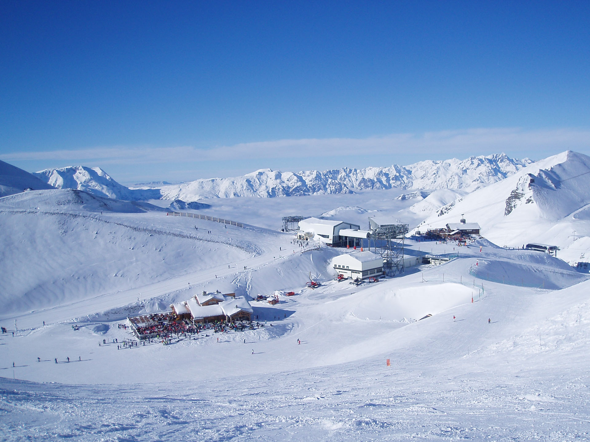 Two mountain restaurants and the top of a chair lift sit atop a mountain above a sea of clouds in Les 2 Alpes