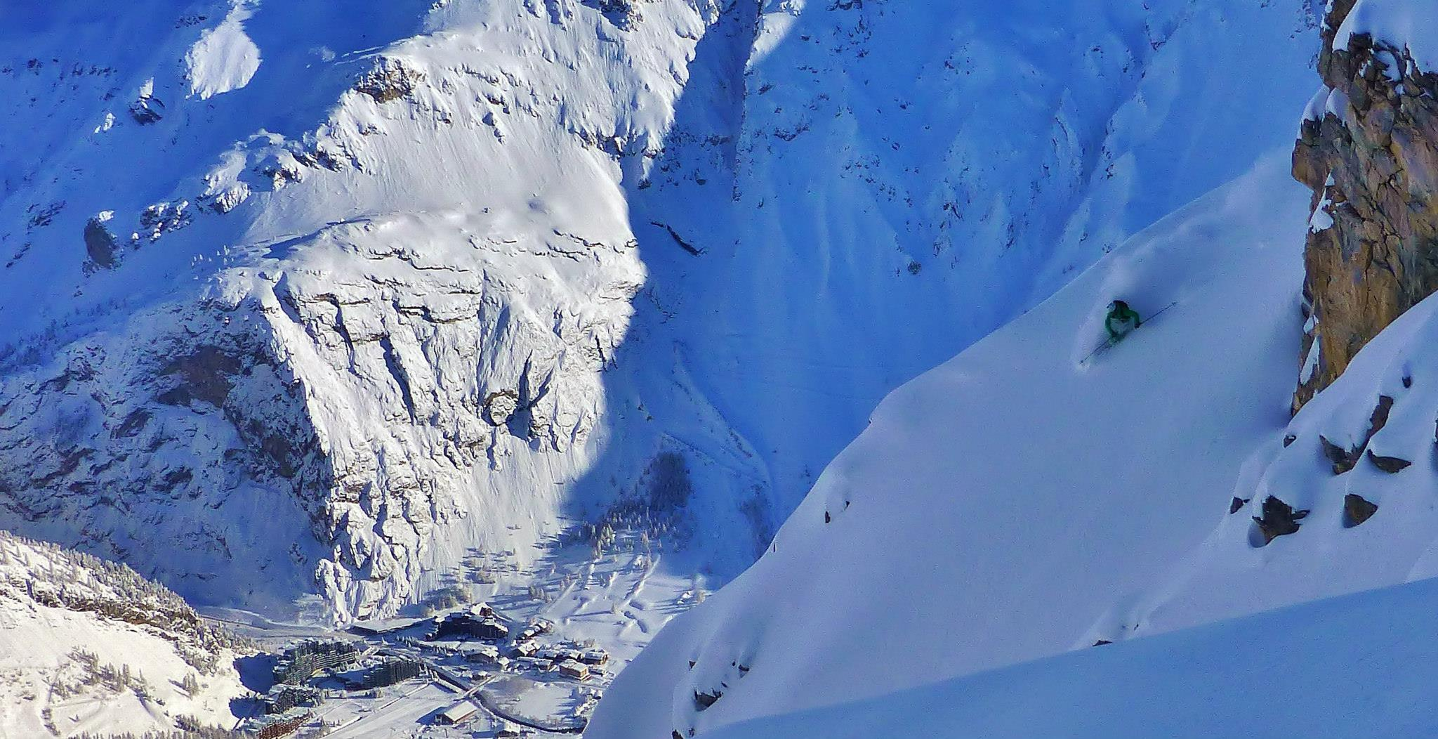 Skier making big powder turn in entrance to Table couloir Val d'Isere