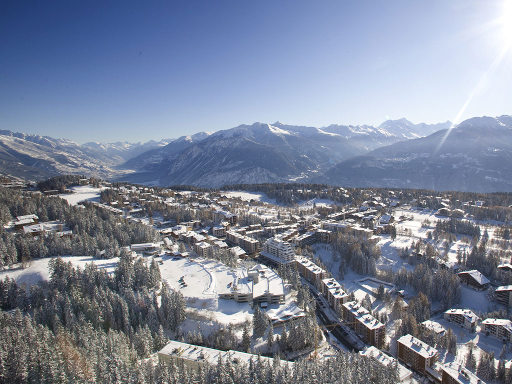 The alpine village of crans montana, nestled between mountains under a sunny sky