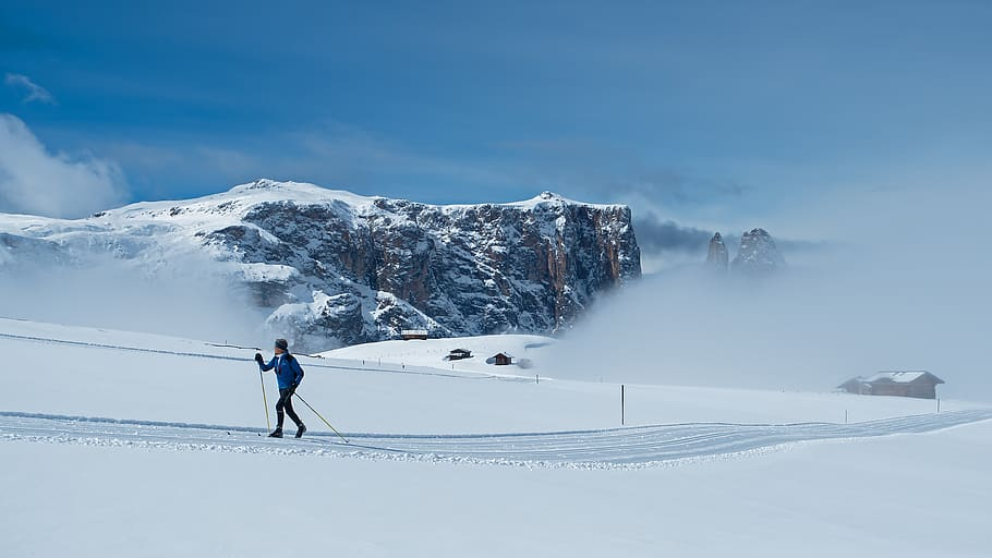 Woman in blue cross-country skiing in front of mountains and low clouds