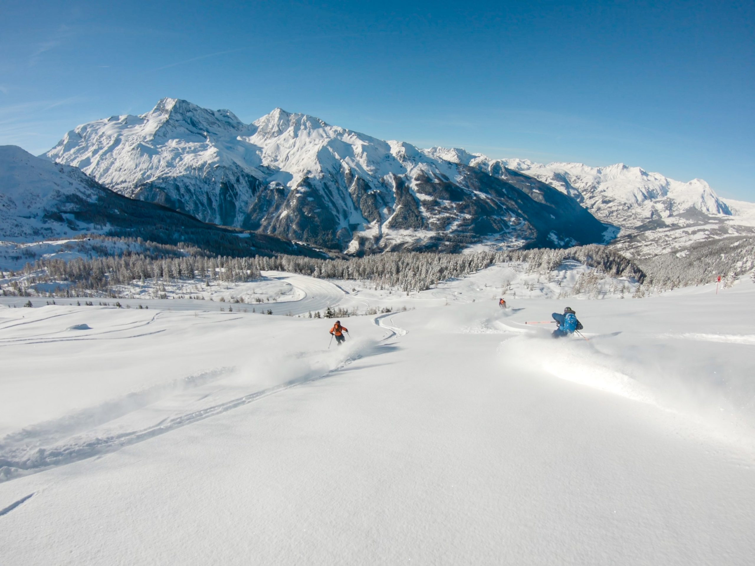 Two skiers ski through a field of powder towards a large mountain in Ste Foy