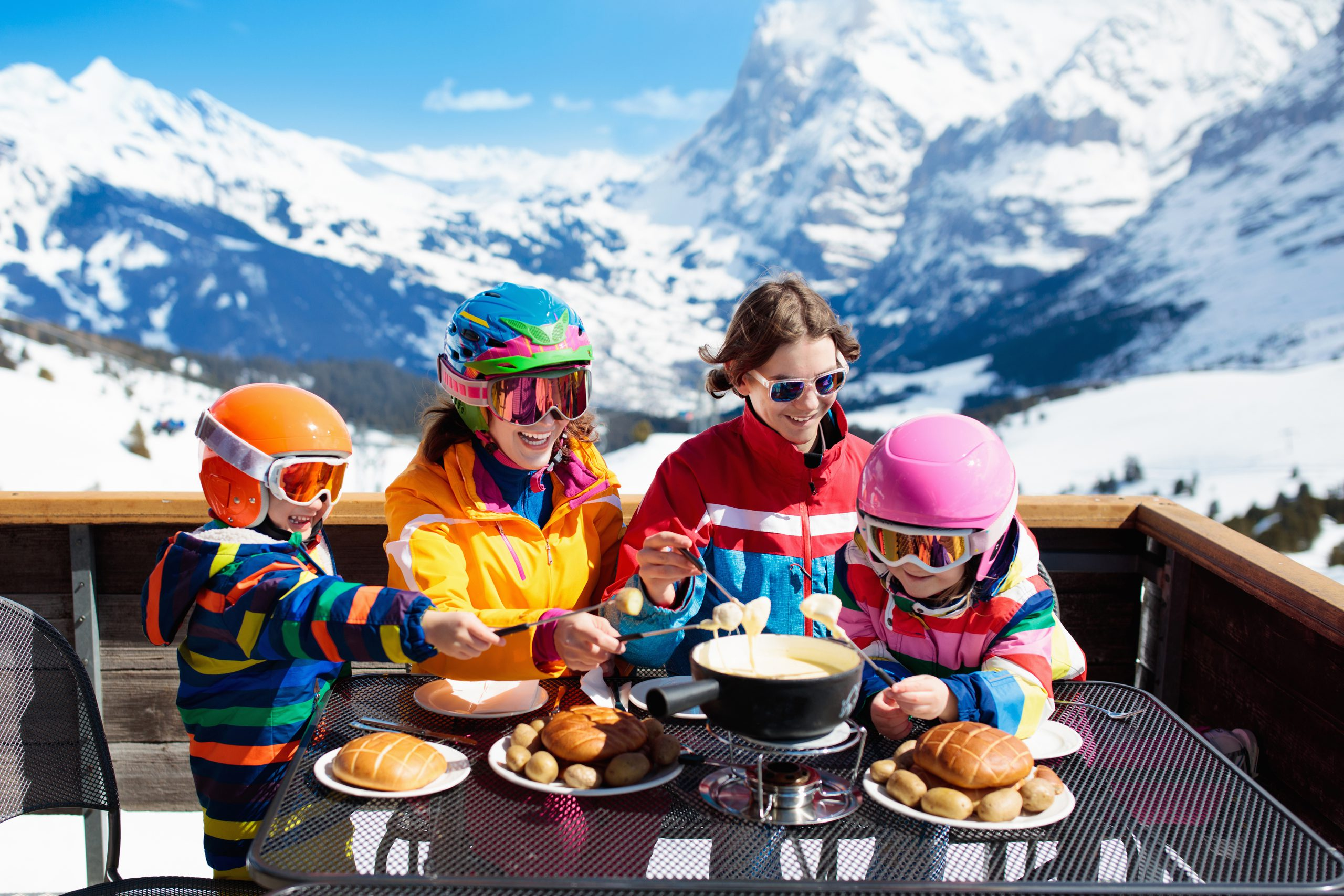 Family with children enjoying apres ski lunch with traditional Swiss raclette and cheese fondue in restaurant on top of snow covered mountain on winter or Christmas vacation. Parents and kids skiing.