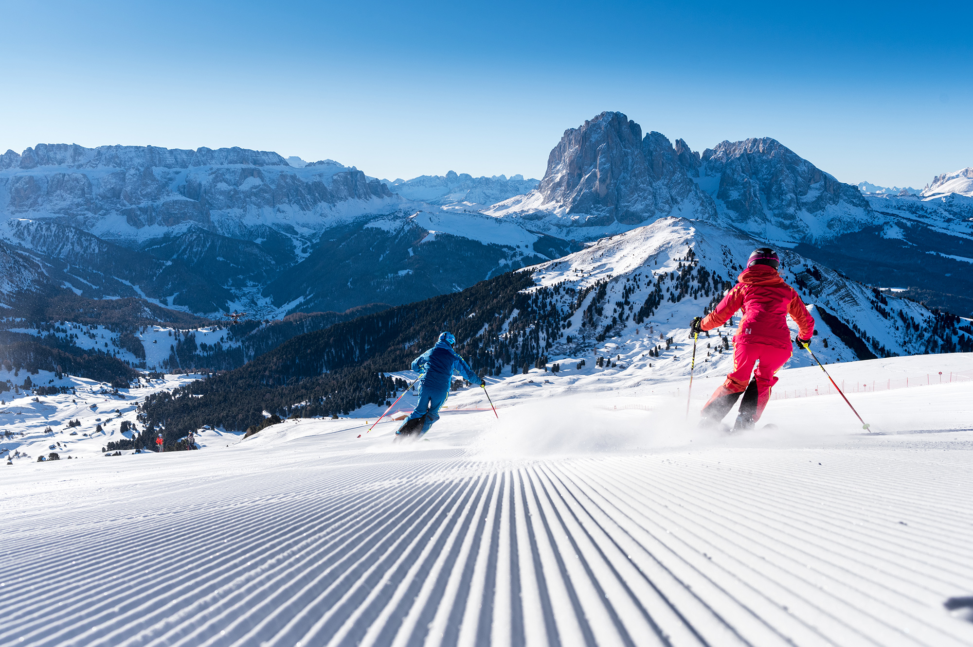 two skiers enjoy a perfectly groomed blue piste in val gardena