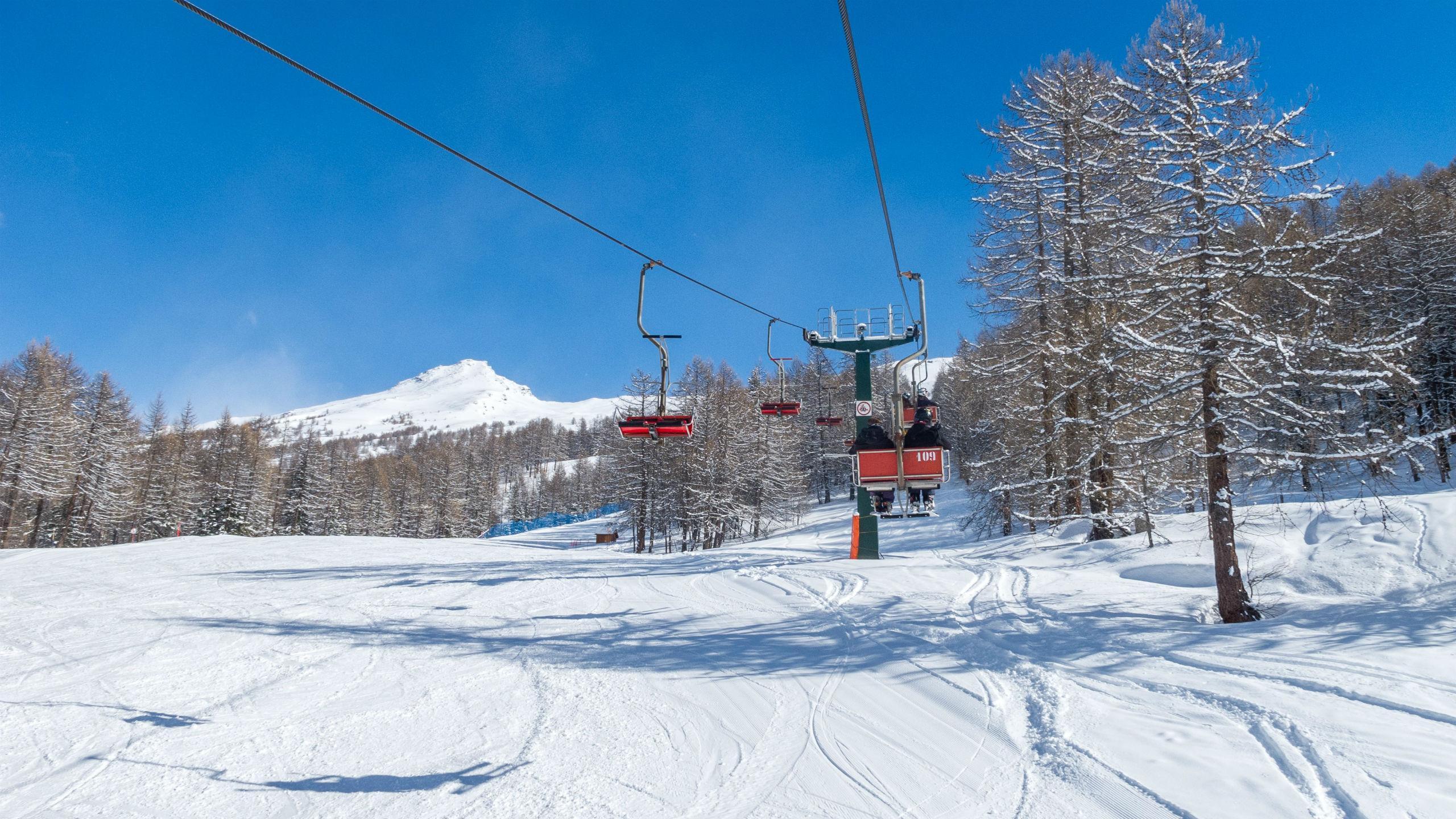 two skiers on a beginner ski lift in bardonecchia