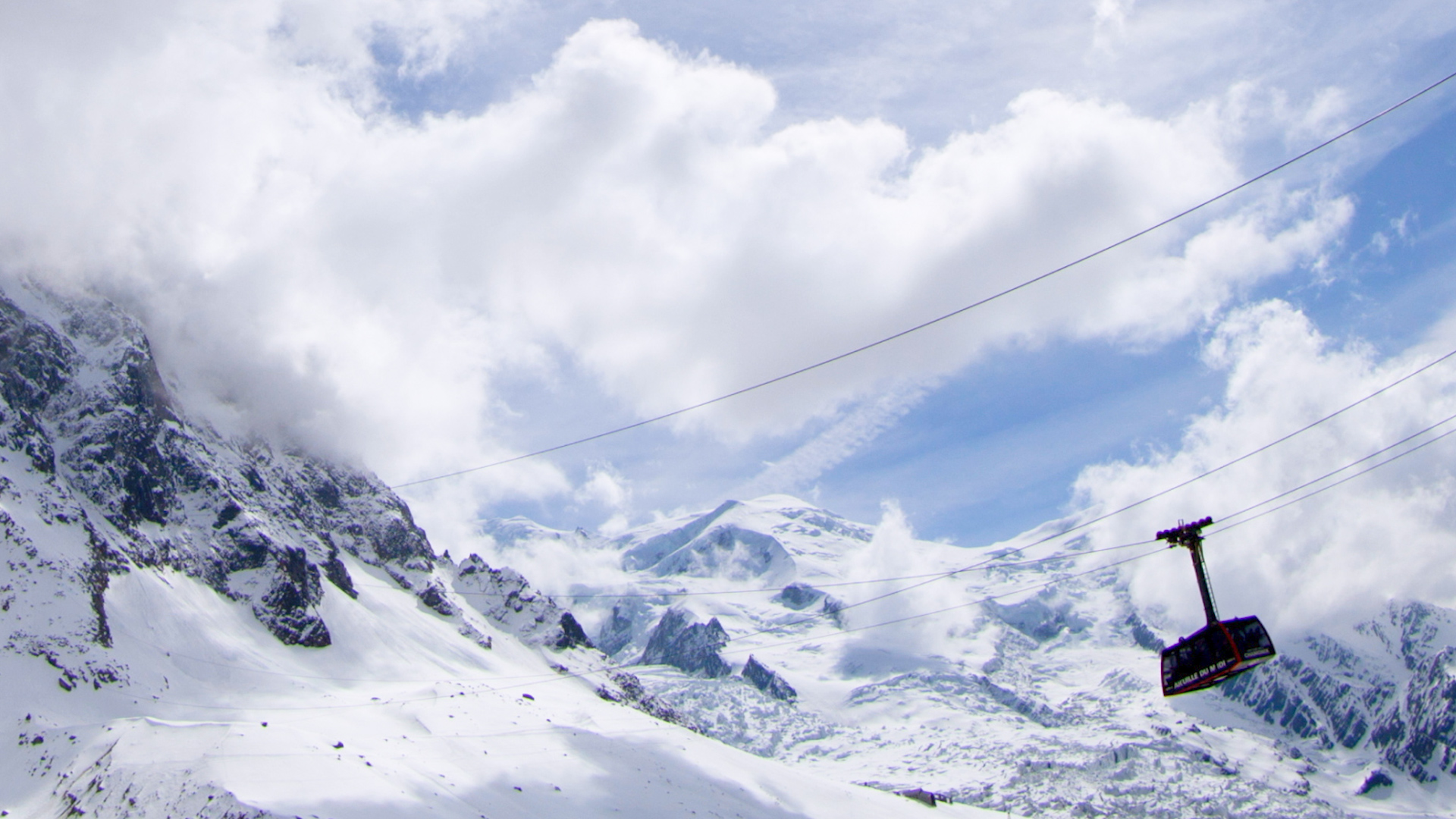 The Aiguille du Midi Cable car rises into the clouds in Chamonix