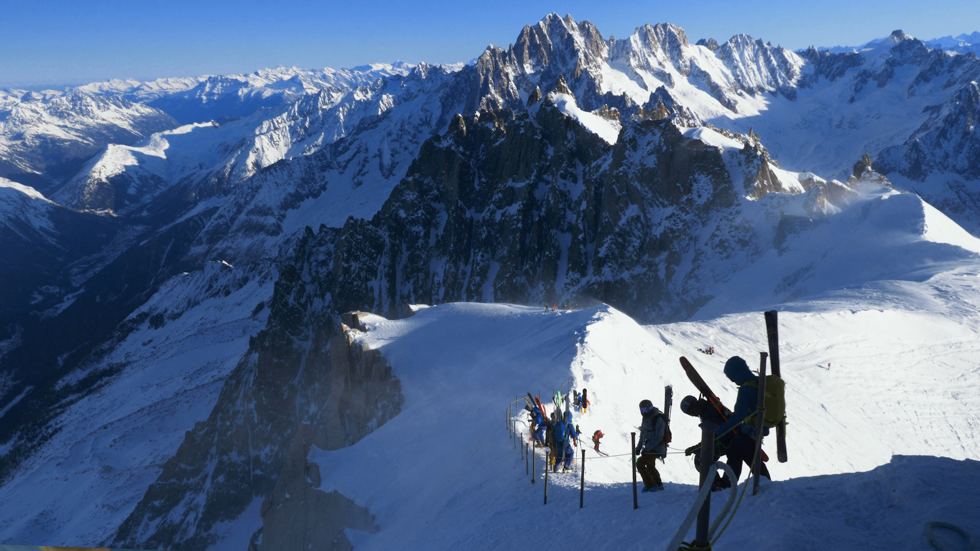 Skiers walk down the snowy ridge of the Arete towards the Vallee Blanche below