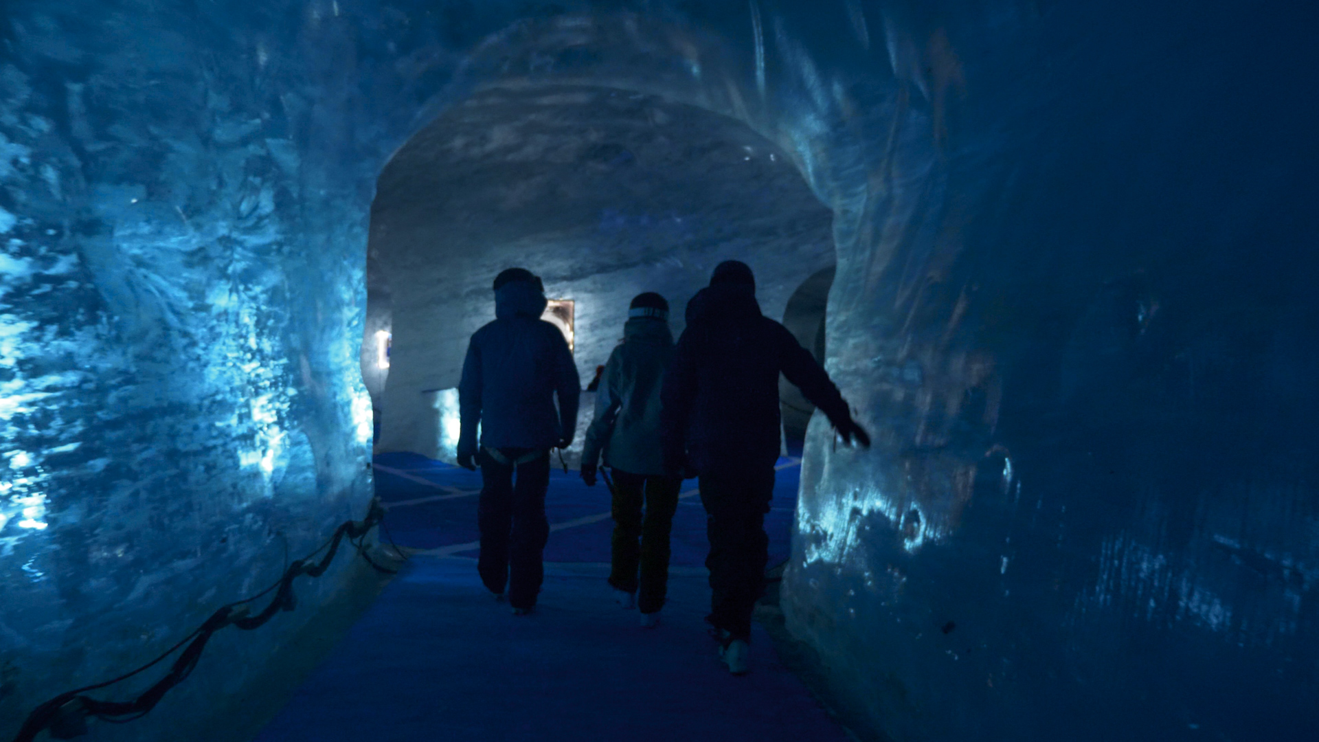 Three skiers walk through a cave of blue ice on their way back from the Vallee Blanche