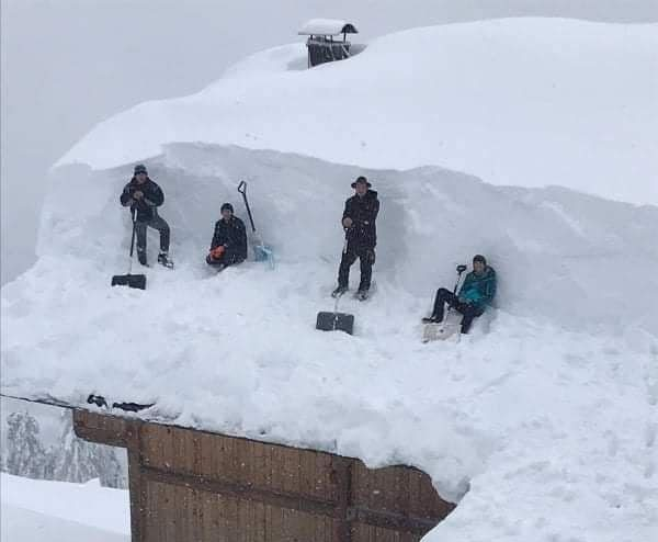 Four men clear heavy snowfall from a roof in Kochberg, Austria