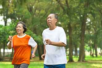 A woman and a man exercise in a park.