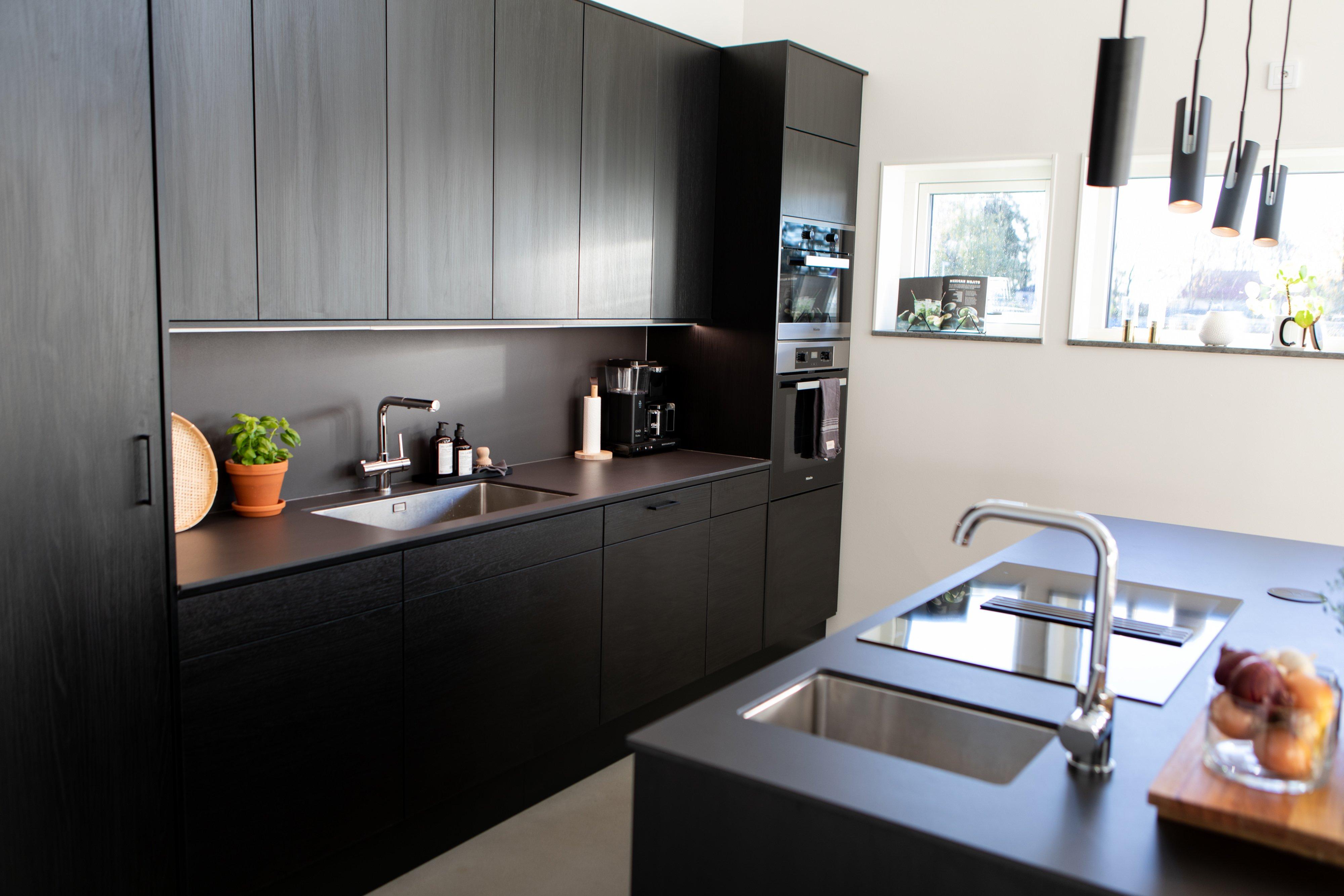 Svart stilrent kök utan synliga handtag och dold fläkt i hällen — Villa Elofsson Skövdevillan