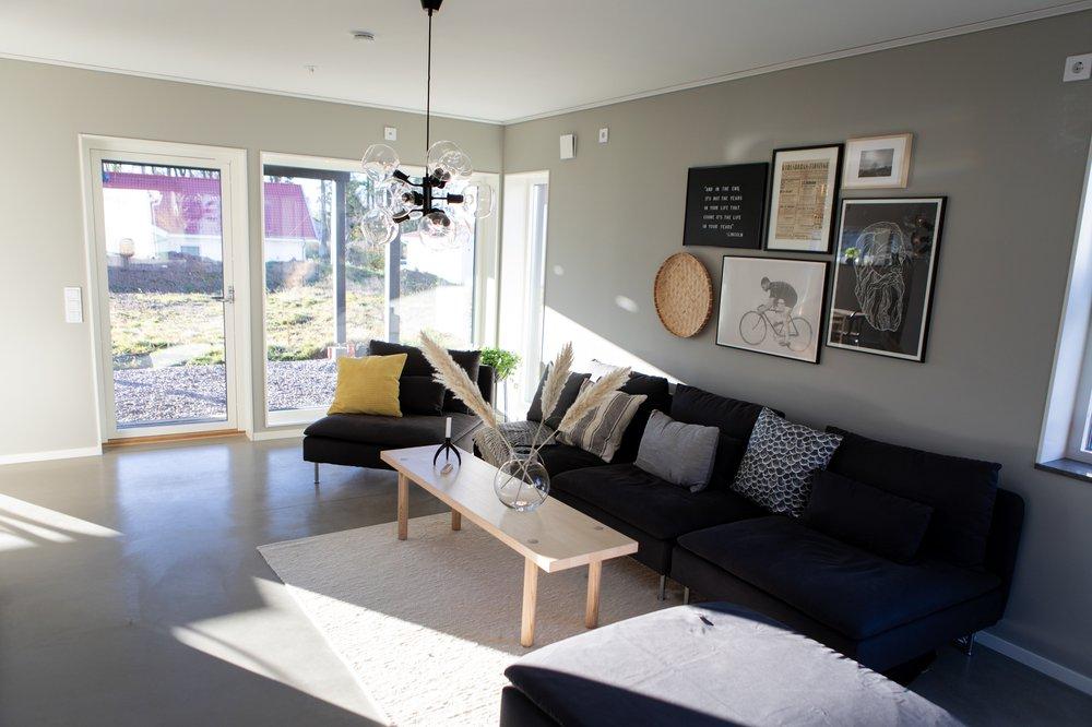 Vardagsrum med med fönster och glasdörr mot baksidan — Villa Elofsson Skövdevillan