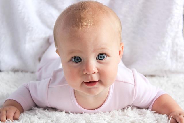 Portrait d'un bébé aux yeux bleuxs, de face, couché sur le ventre sur un tissu blanc.