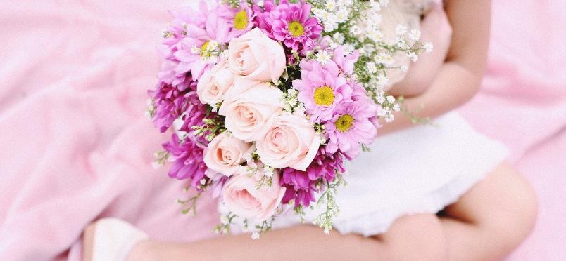 Enfant tenant un joli bouquet de fleurs roses en main.