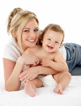 Une maman tient son enfant dans les bras, ils sourient à la caméra.
