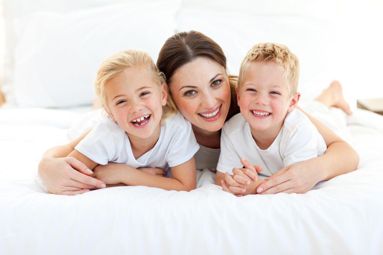Portrait d'une jeune Maman avec deux enfants sur un lit