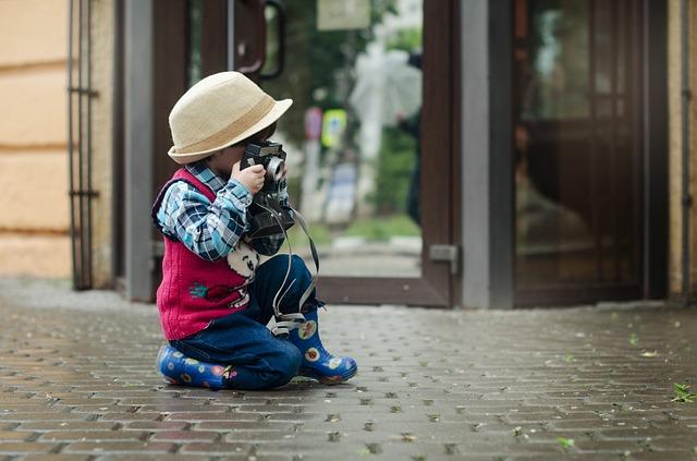 Enfant assis par terre avec un appareil photo en main, prêt à photographier.