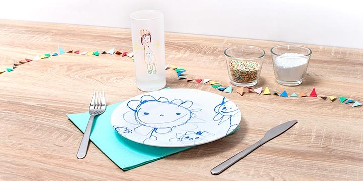 Glas und Teller mit Kinderzeichnung