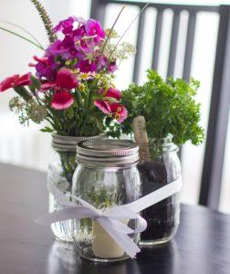Einmachgläser mit Blumen und Kerze als Geschenk