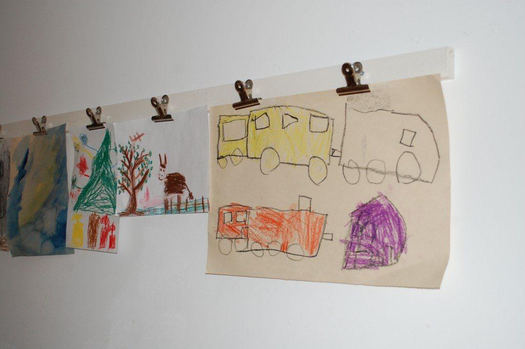 Bilderleiste mit aufgehängten Kinderzeichnungen