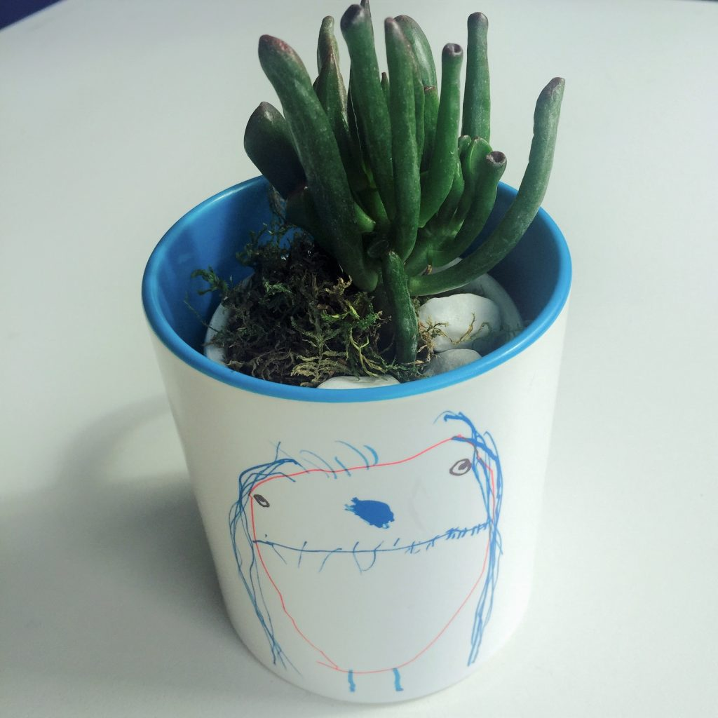 Tasse mit Kinderzeichnung und Pflanze