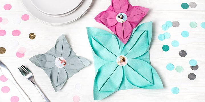 Personalised napkin stickers on colorful napkins folded like flowers
