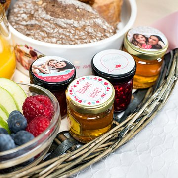 Detail of Mother's Day breakfast basket with fruit, bread and little jars of jam