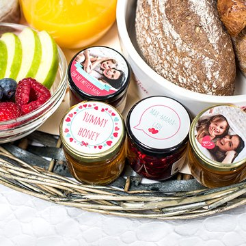 Detail of breakfast basket with fruit, bread and little jars of jam