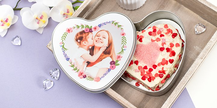 Frosted heart shaped chocolate cake in heart shaped cookie tin