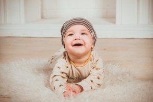 Portrait d'un jeune bébé couché sur le ventre, qui relève la tête et sourit