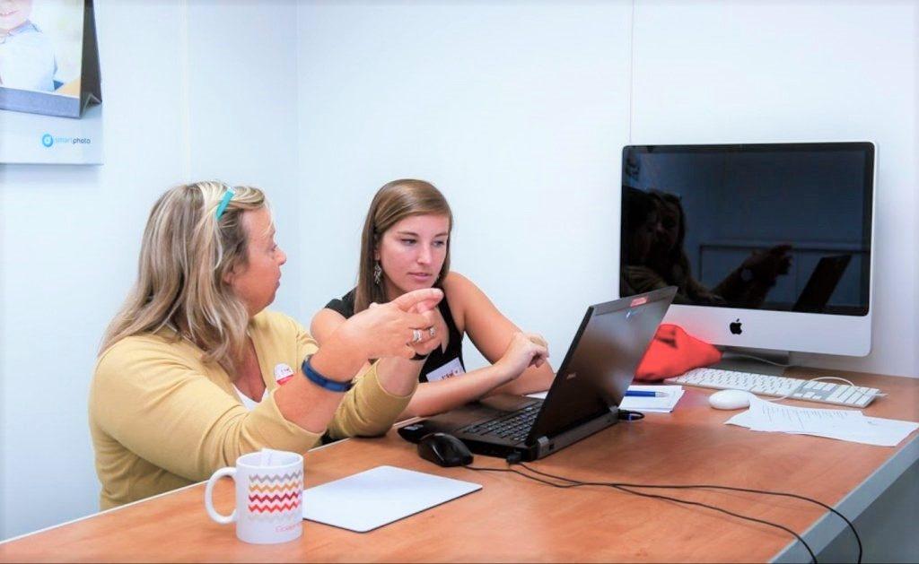Dialogue avec les client smartphoto - discussion entre deux personnes devant un ordinateur