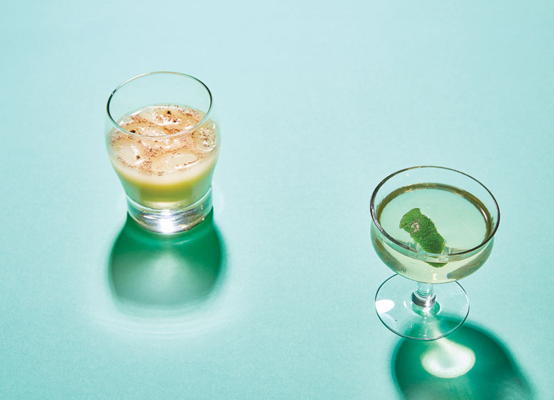 two soju cocktails in small glasses on blue background