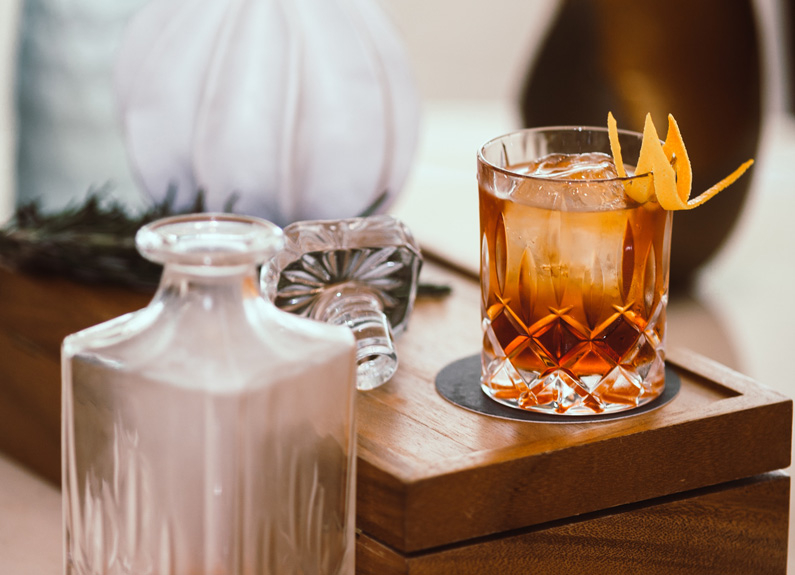 a rocks glass of rum with a large cube of ice next to a decanter