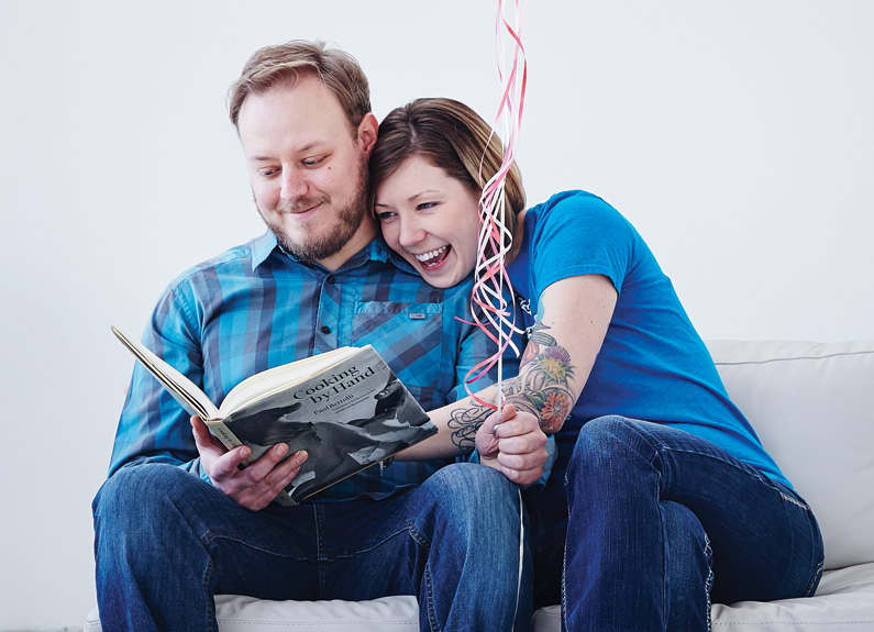 a woman in blue shirt hugging a bearded man in a blue shirt reading a book and holding pink balloon strings