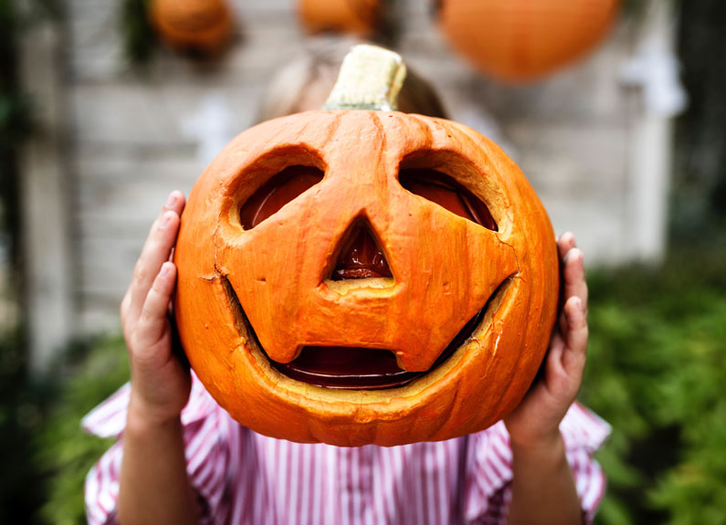 child holding a jack-o-lantern in front of their face