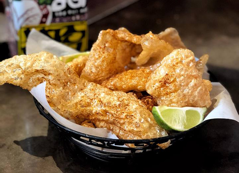 a basket of chicharrones with a lime wedge