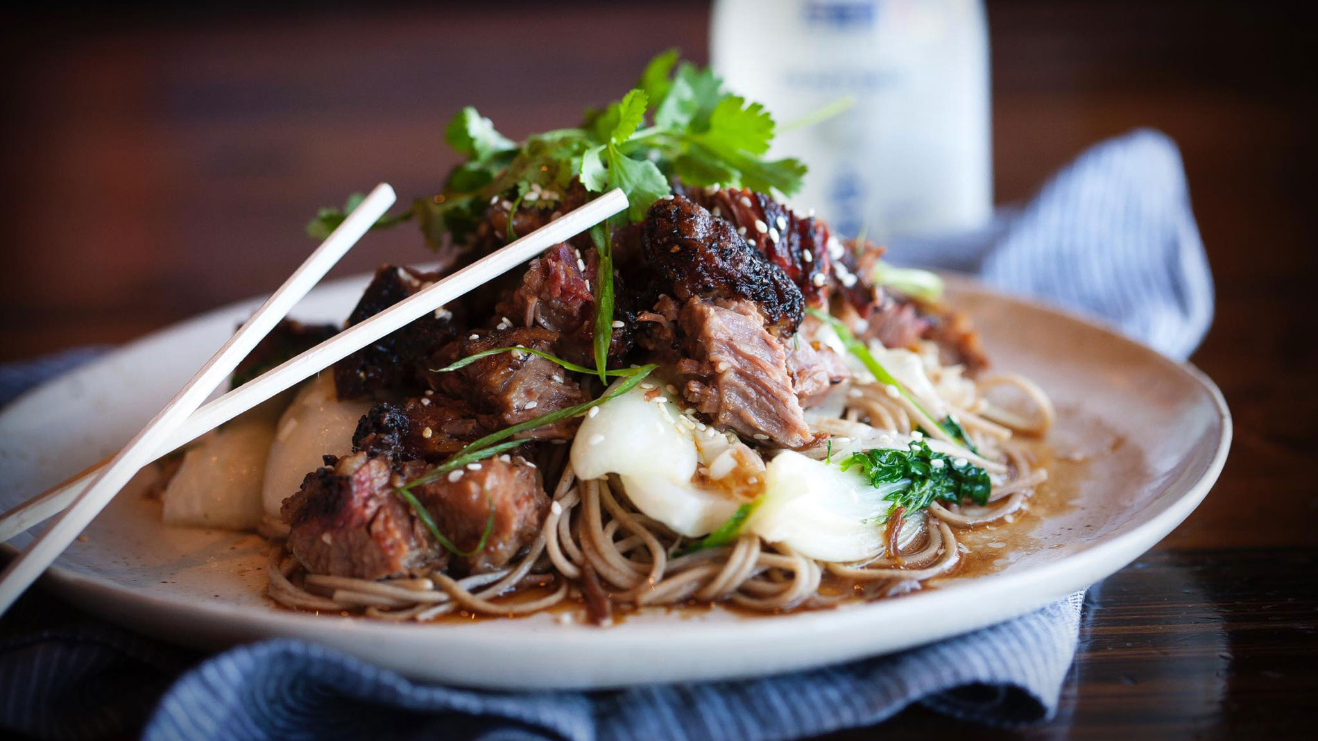 a dish piled with soba noodles and burnt ends with chopsticks