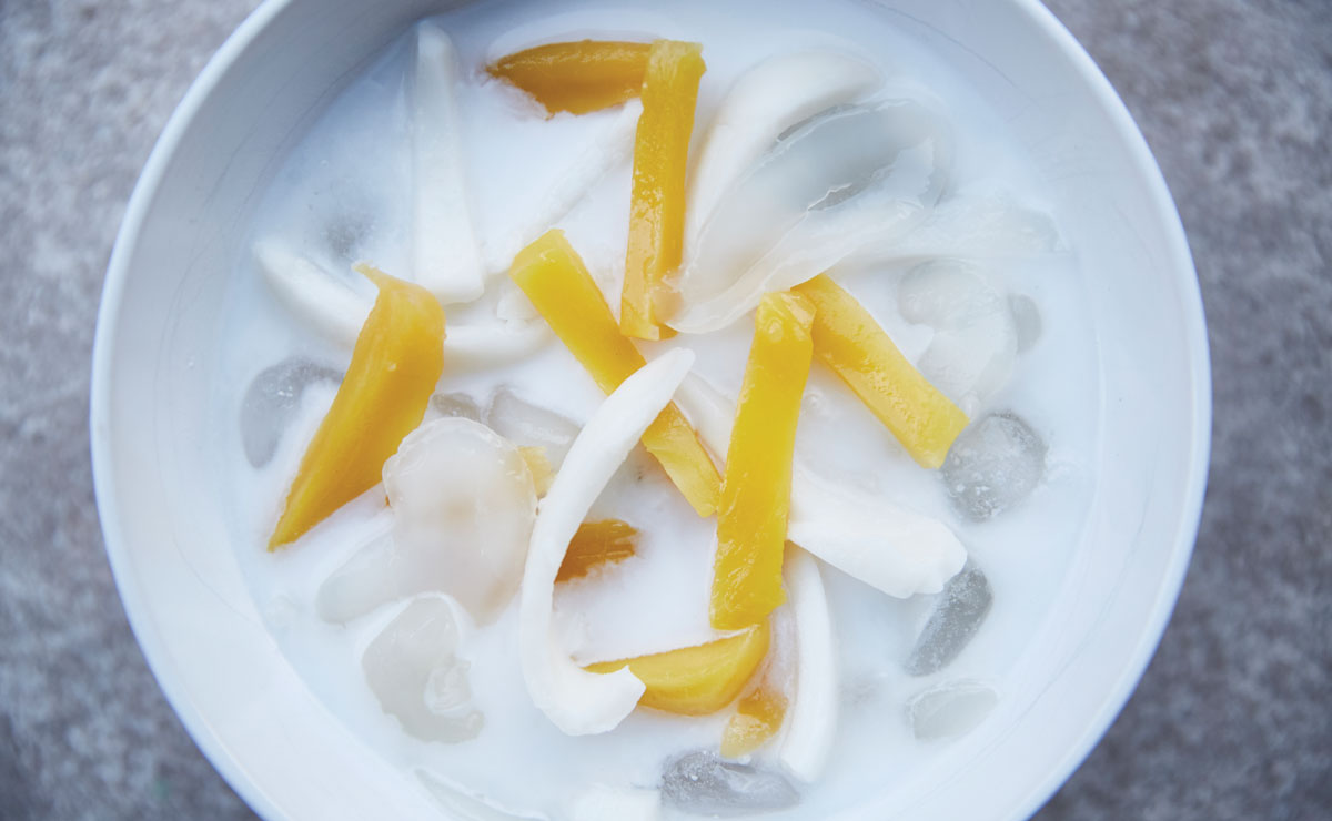 a bowl of coconut milk with jackfruit, coconut meat and palm seeds
