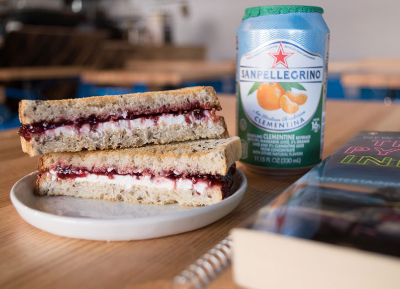 goat cheese and jam sandwich next to a can of san pellegrino sparkling water and a book