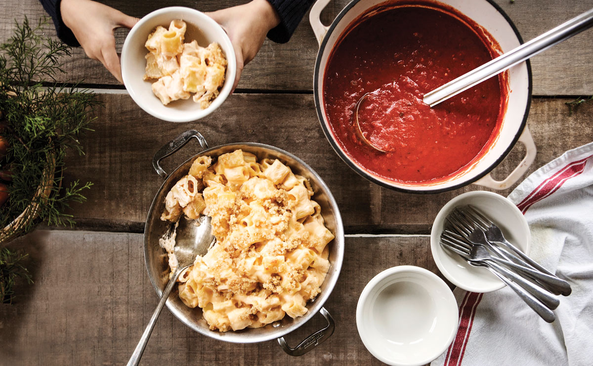 a pot of macaroni and cheese with a pot of red sauce