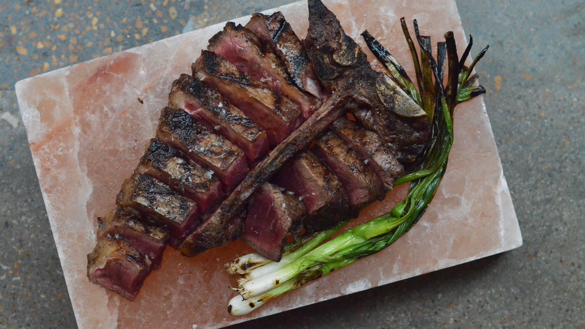 a bone-in porterhouse steak sliced up atop a pink salt block with grilled green onions