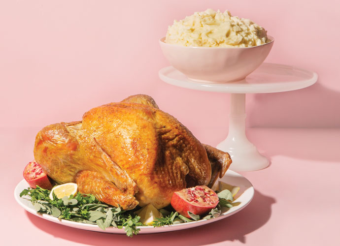a roast turkey and a bowl of mashed potatoes on a cake stand on a pink background