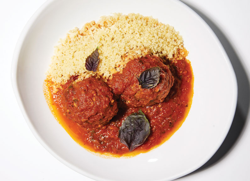 two lamb meatballs covered in red sauce next to a bed of couscous on a white plate