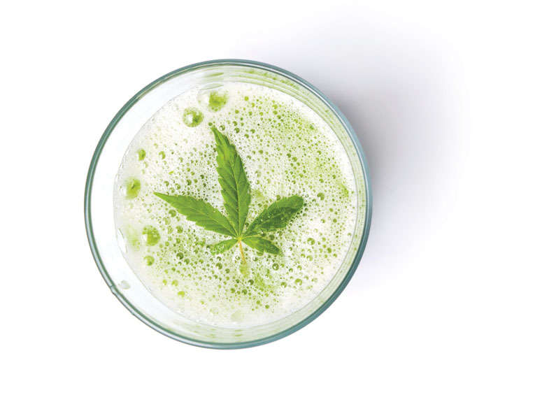a greens smoothie with a marijuana leaf on top.