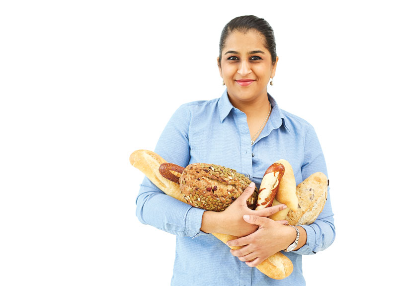 a woman in a blue shirt holding a large armful of bread