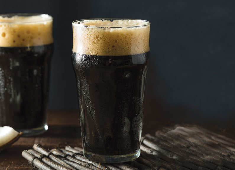 two imperial pint glasses with dark beer